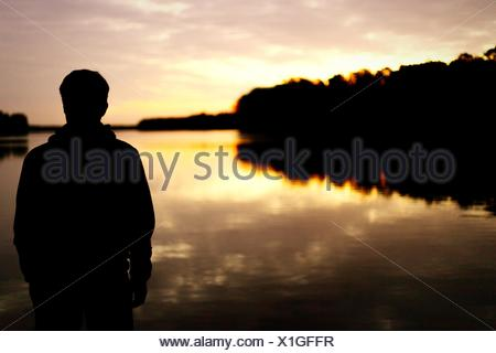 Rear View Of Silhouette Man Standing In Front Of Lake During Sunset