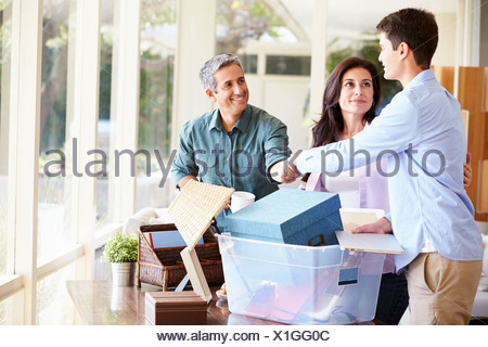 Parents Helping Teenage Son Pack For College - Stock Photo