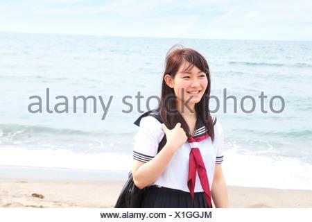 Young woman standing on beach wearing school uniform - Stock Photo