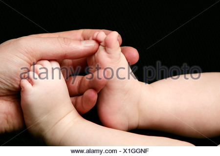 An adult hand and baby feet close-up. - Stock Photo