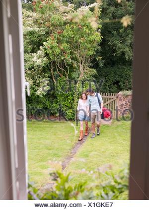 couple walking along path towards house - Stock Photo