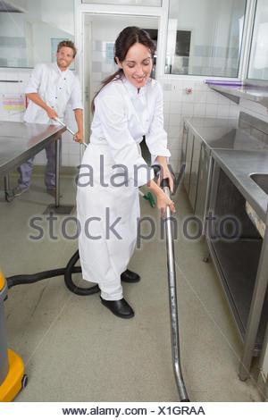 restaurant staff cleaning kitchen floor - Stock Photo