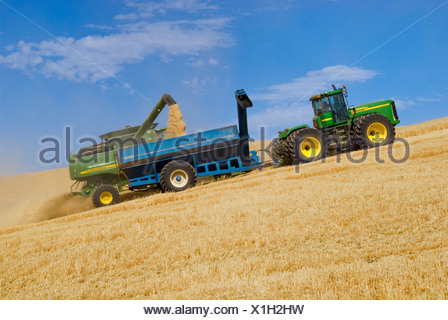 """A John Deere combine harvests barley on steep hillside terrain and unloads the harvested barley into a grain cart """"on-the-go"""". - Stock Photo"""