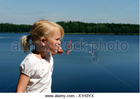 Side view of a girl blowing soap bubbles against peaceful lake