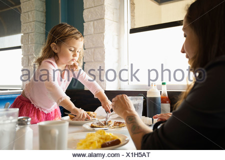 Mother and toddler daughter eating in diner - Stock Photo