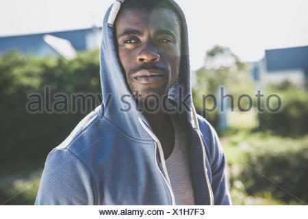 Portrait of man wearing hooded top looking away - Stock Photo