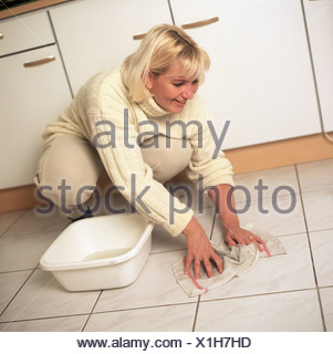 35+ natural woman cleaning the floor, could be housewife, charlady or elderly help. - Stock Photo