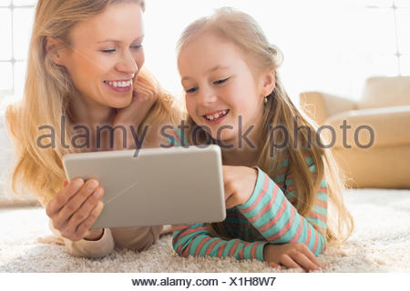 Happy mother and daughter using digital tablet on floor at home - Stock Photo