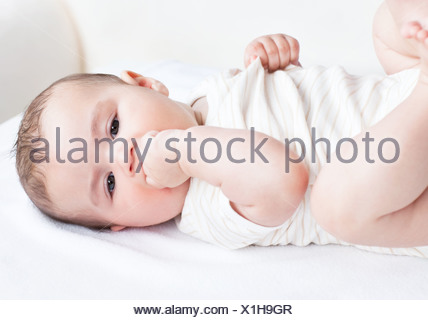 Portrait of a cute newborn baby lying on the sofa in his bedroom - Stock Photo