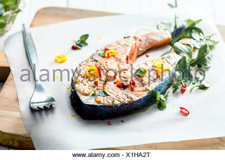 Cutlet of grilled gourmet salmon seasoned with fresh herbs and spices served on a wooden board in a seafood restaurant , low angle view - Stock Photo