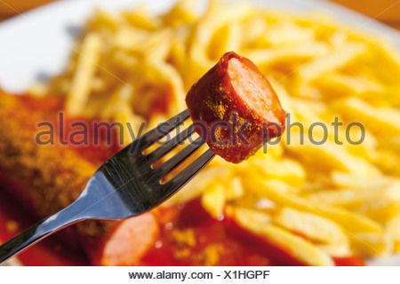 Curry sausage on fork with chips in background - Stock Photo
