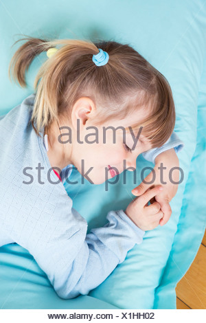 Portrait of little girl sleeping on bean bag, elevated view - Stock Photo