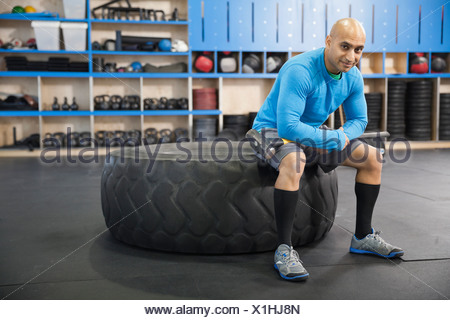Man sitting in Crossfit gym on tire - Stock Photo