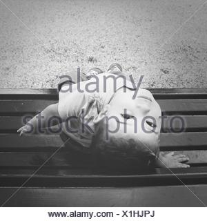 Portrait Of Boy Sitting On Bench In Park - Stock Photo
