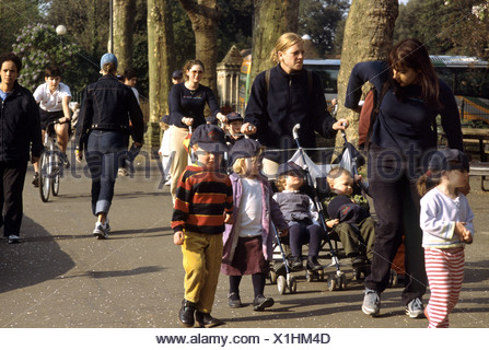 mothers walking with children through the park after school - Stock Photo