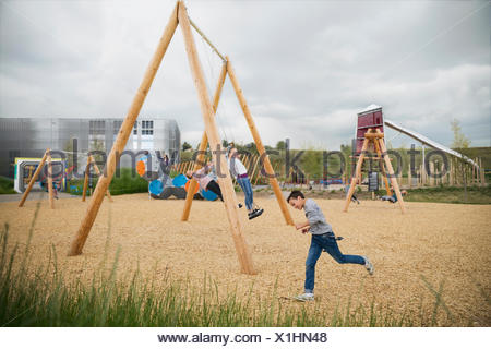 Kids playing at swings at playground - Stock Photo
