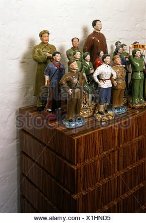 Communist ceramic figurines arranged on a wooden cabinet - Stock Photo