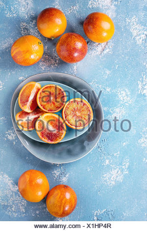Sliced and whole ripe juicy Sicilian Blood oranges fruits on ceramic plate over blue concrete texture background. Top view - Stock Photo