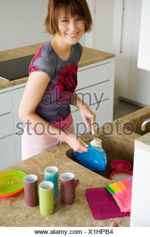 Young woman washing the dishes - Stock Photo