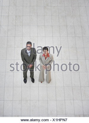 Two businesspeople standing indoors looking at camera - Stock Photo