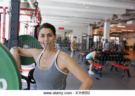 Portrait confident woman leaning on barbell at gym - Stock Photo