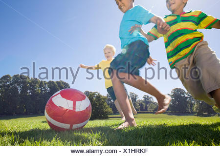 Smiling boys playing soccer in park - Stock Photo
