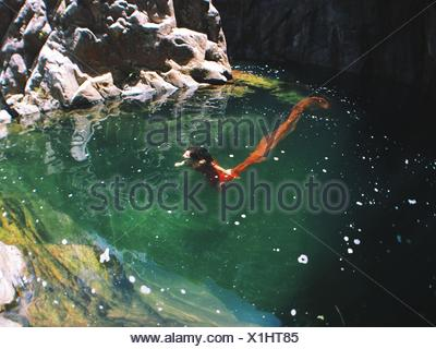 Woman in red dress underwater - Stock Photo