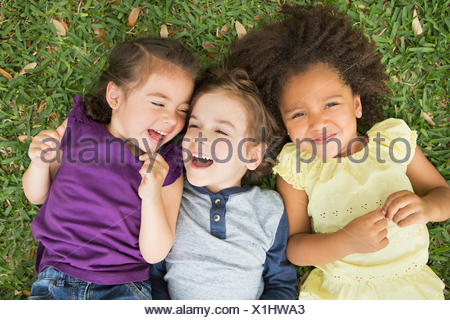 Three children lying on their backs on the grass, looking up and laughing. - Stock Photo
