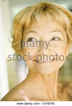 Senior woman with dollops of moisturizer under eyes - Stock Photo