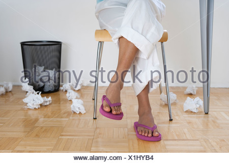 Female feet in thongs with crumpled papers