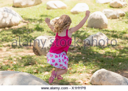 Young girl jumping from boulders in park - Stock Photo
