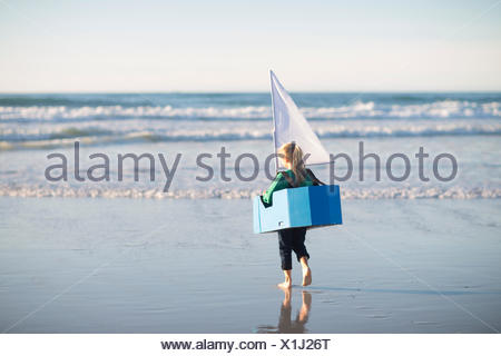 Girl running with toy boat into sea - Stock Photo