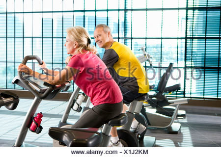 Couple riding exercise bikes in health club - Stock Photo