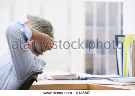 Business man with hands behind head in office - Stock Photo