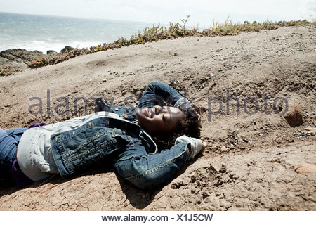 Young woman lying on rocks - Stock Photo