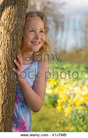 Girl hiding behind tree - Stock Photo