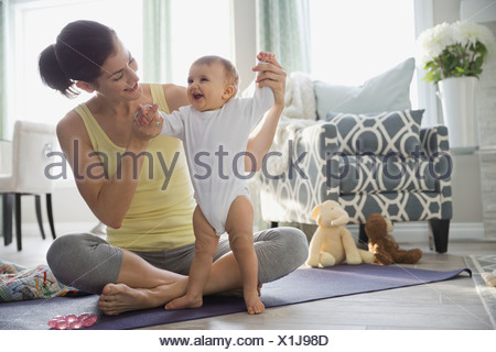 Mother playing with baby on yoga mat at home - Stock Photo
