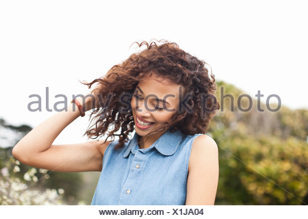 Young woman with hand in hair, smiling - Stock Photo
