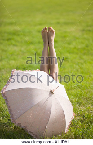 Young woman lying in grass, behind an umbrella - Stock Photo