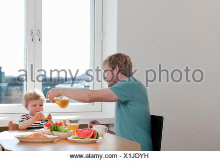 Father and toddler son having breakfast at kitchen table - Stock Photo