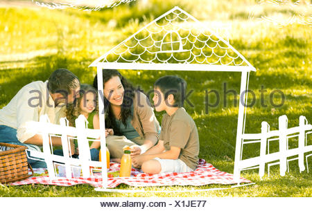 Composite image of family picnicking together - Stock Photo