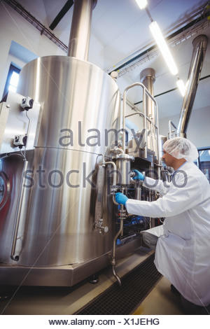Manufacturer kneeling while working in brewery - Stock Photo