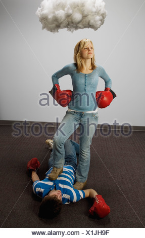 Male and female fighting under cloud - Stock Photo