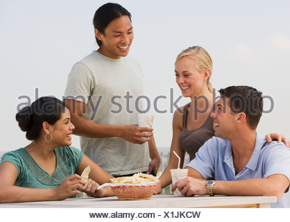 Multi-ethnic friends eating - Stock Photo