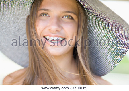 Teenage girl in braces wearing sunhat - Stock Photo