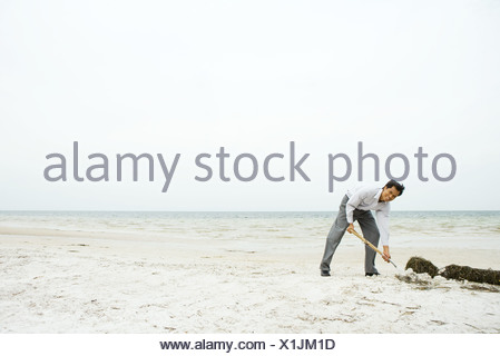 Man at the beach, bending over and digging in sand, smiling at camera - Stock Photo