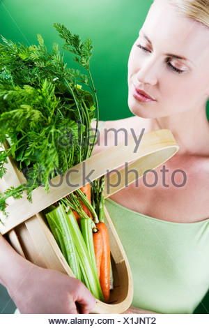 A young woman holding a basket full of vegetables - Stock Photo