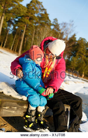 Sweden, Sodermanland, Jarna, Mother with son (2-3) sitting on wooden bench in winter - Stock Photo