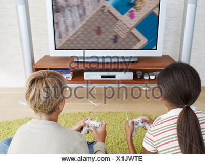 Two young kids playing video games - Stock Photo