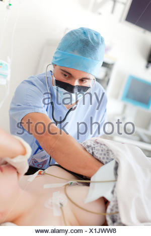 Anaesthetist male nurse examining a female patient, Operating room, Bordeaux hospital, France. - Stock Photo